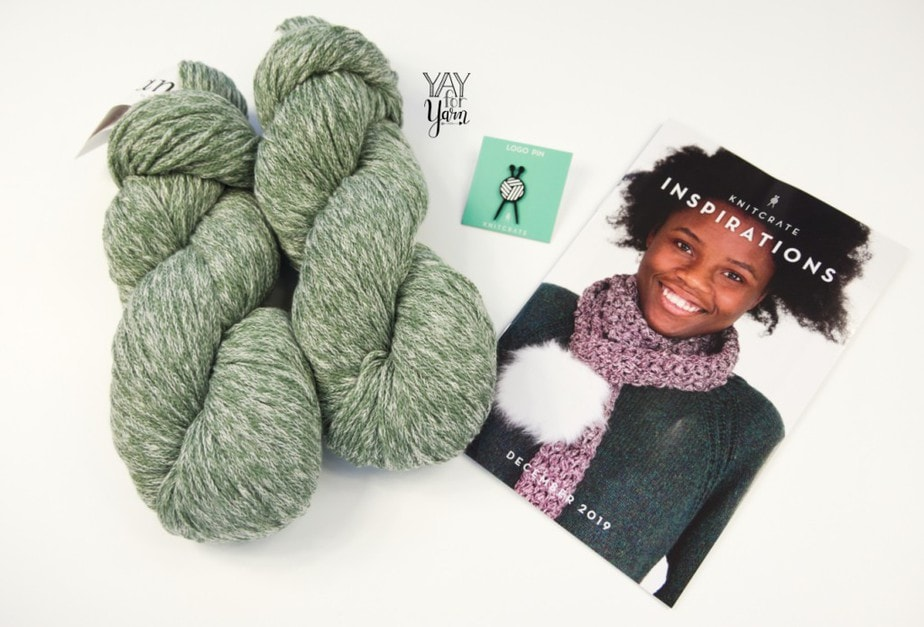 knitcrate contents for december 2019 - pattern book, logo pin, and marled chainette yarn