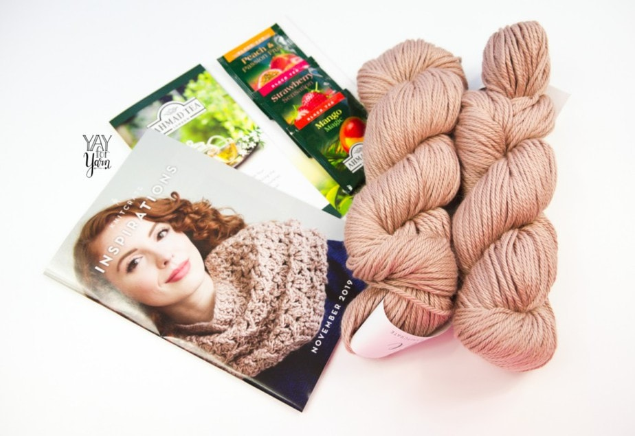 contents of the november 2019 knitcrate - two skeins of silk yarn, pattern book, and tea samples