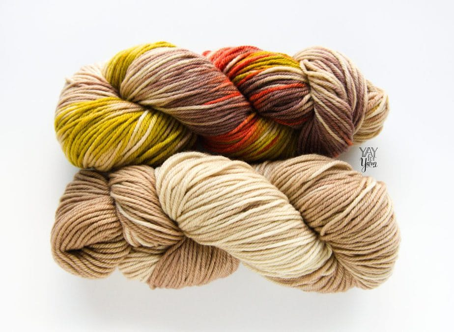 2 skeins of hand dyed yarn - beige tan semisolid and brown red green beige variegated