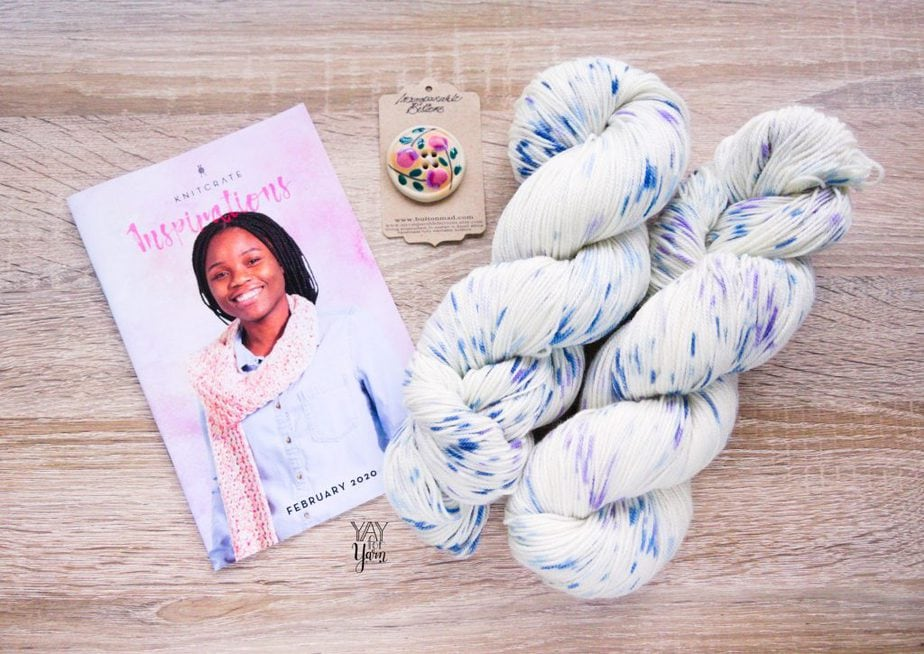two skeins of speckled hand dyed yarn with handmade button and pattern booklet