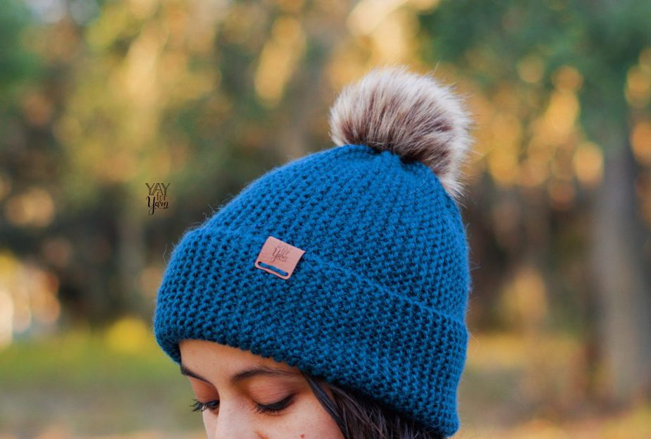 blue toque hat with brim and pom pom