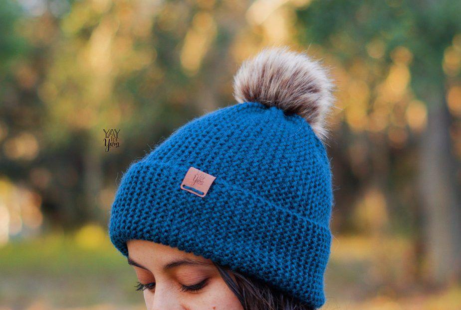 blue toque hat with brim and pom pom