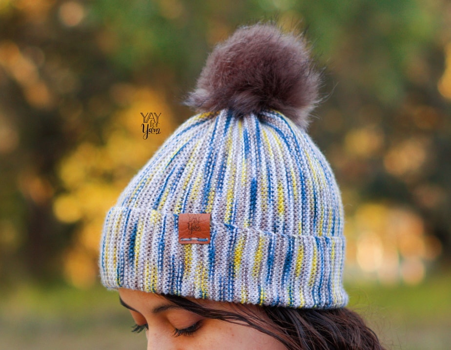 blue, yellow, beige, and white hand dyed knit hat with pom pom