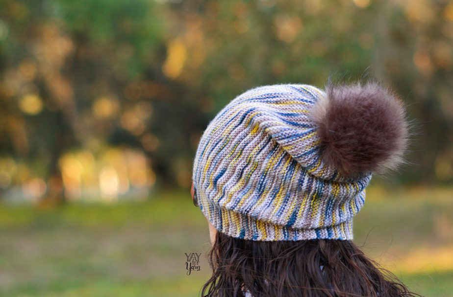 back view, fingering weight sock yarn knitted slouchy hat pattern with faux fur pom pom