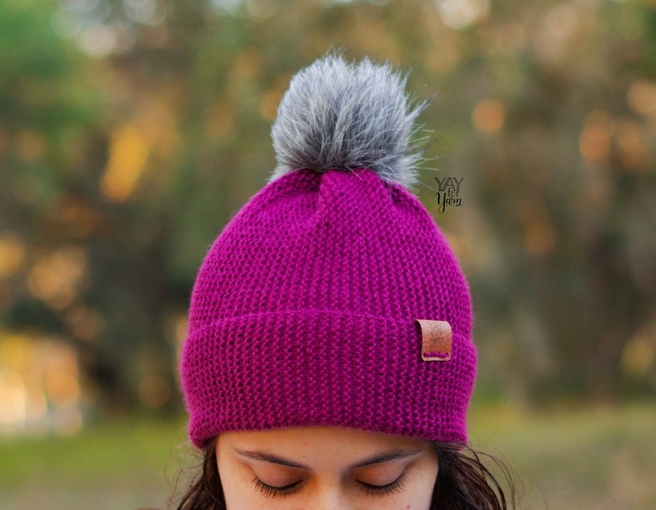 dark purple hat in sport weight yarn with grey faux fur pom pom and leather tag