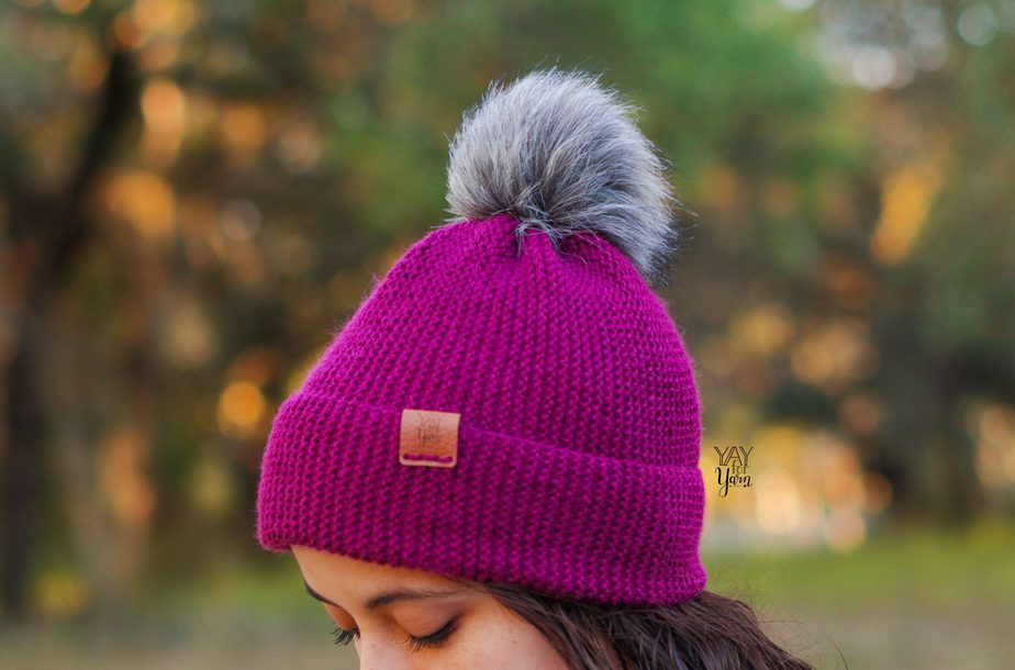 reddish purple winter hat with grey fur pom pom