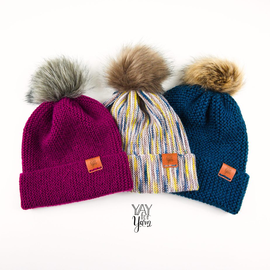 three hand knit hats with faux fur pom poms and leather labels on white background