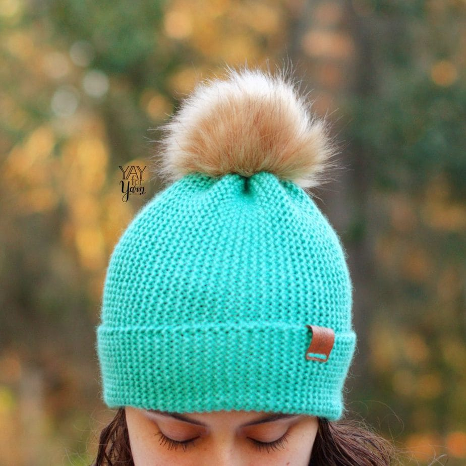 mint green knit hat with light brown faux fur pom pom