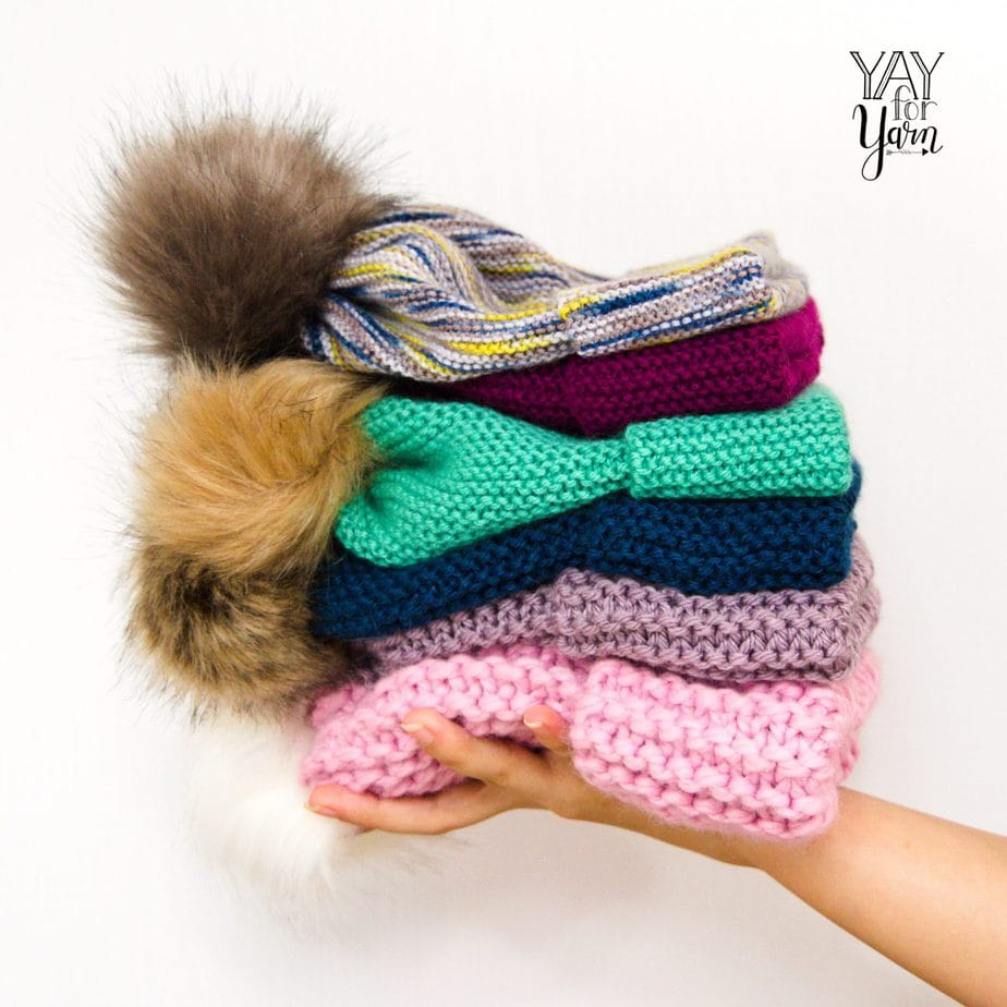 hand holding stack of knitted hats with faux fur pom poms - easiest knitted hat ever knitting pattern