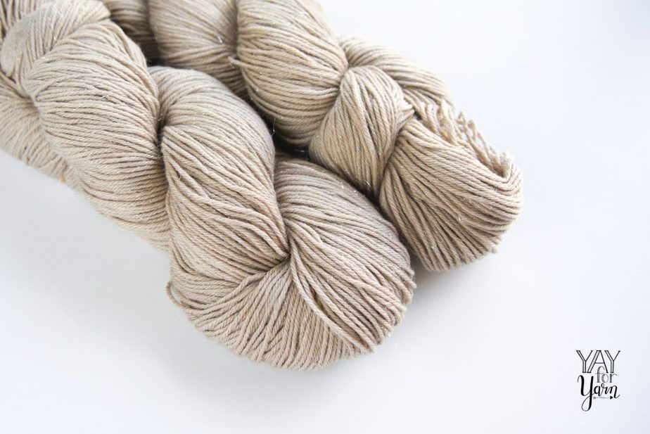 two skeins of sparly beige yarn on white background