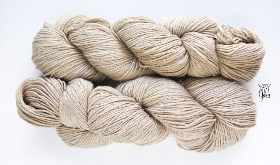 two twisted hanks of sparkly beige sport weight yarn on white background - from april 2020 knitcrate subscription