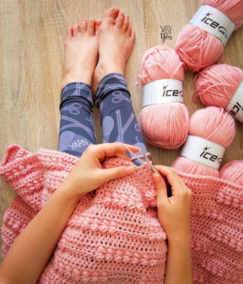 woman crocheting a pink blanket, wearing black yarn-print leggings