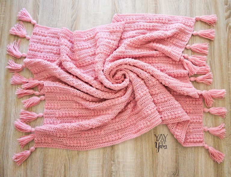 pink crocheted blanket with tassels swirled on the floor