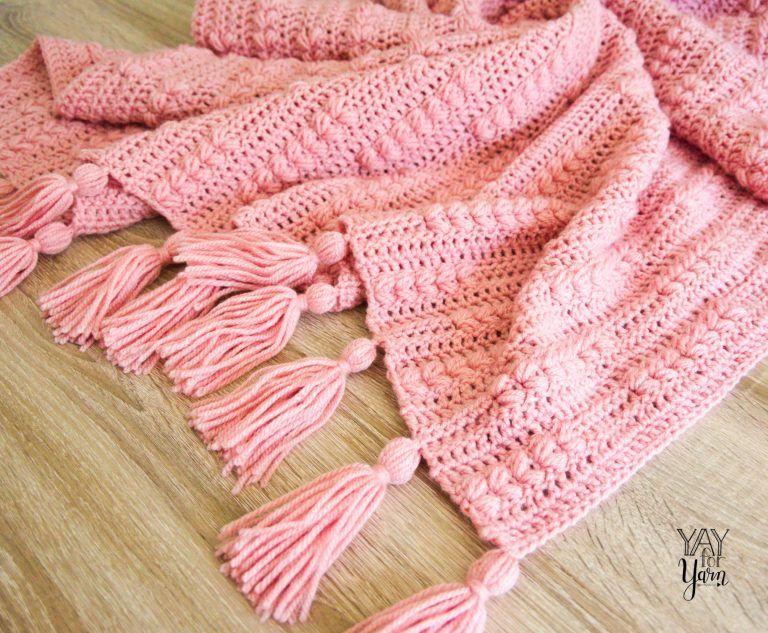 pile of pink crochet blanket with tassels on wood floor