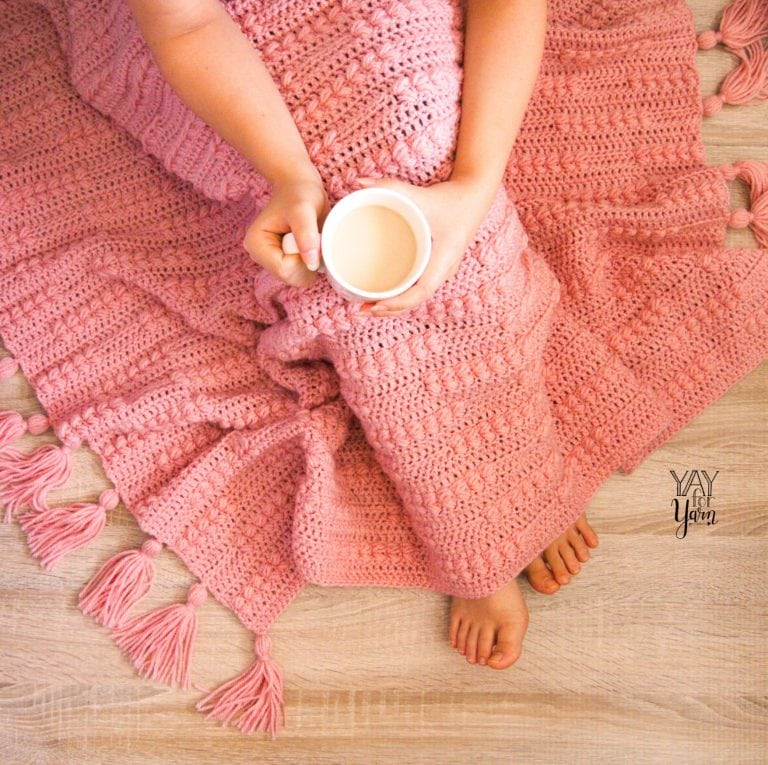 woman under pink crocheted afghan with tassels, holding cup of tea