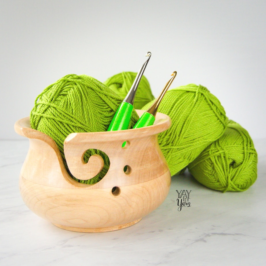 two furls odyssey lime crochet hooks in wooden yarn bowl on marble counter, with lime green skeins of yarn in background