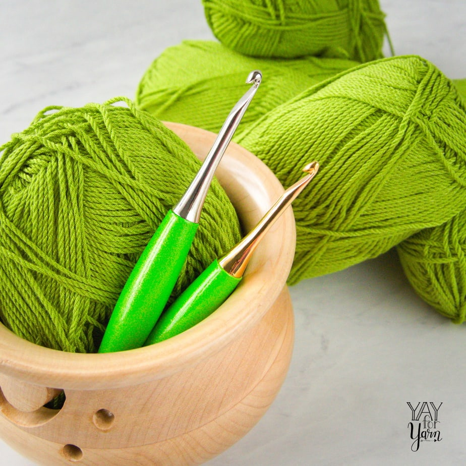 two lime odyssey crochet hooks in wooden yarn bowl in front of lime green yarn on marble counter
