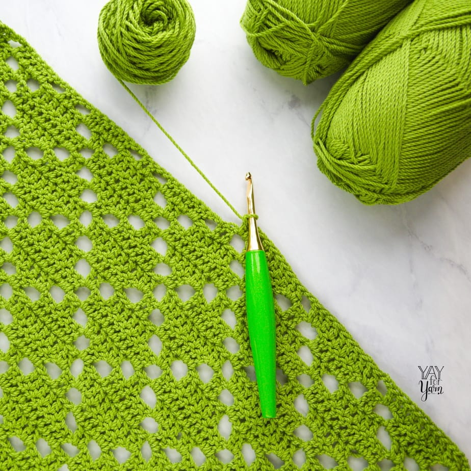 green diamond stitch crochet project with several skeins of green yarn and lime green Furls crochet hook on marble background