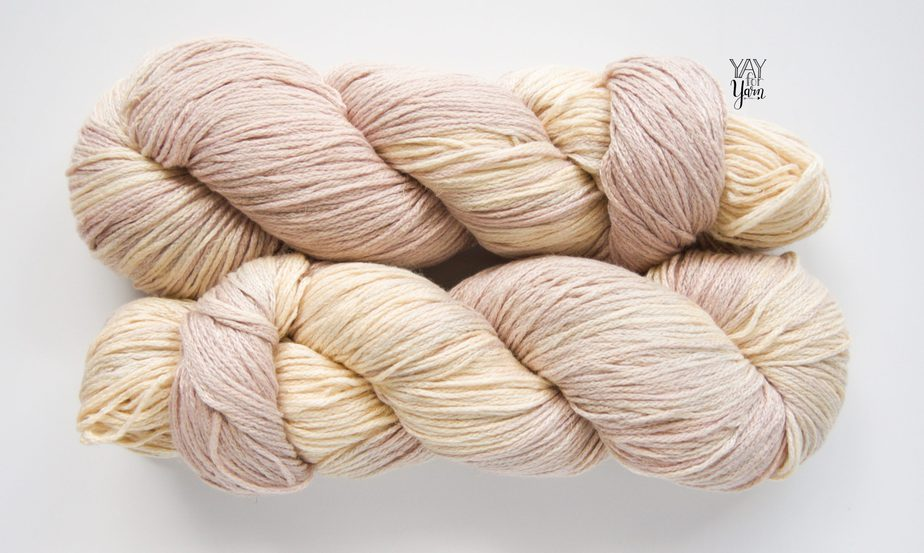 two skeins of beige / sand colored hand dyed yarn laying horizontally on white background