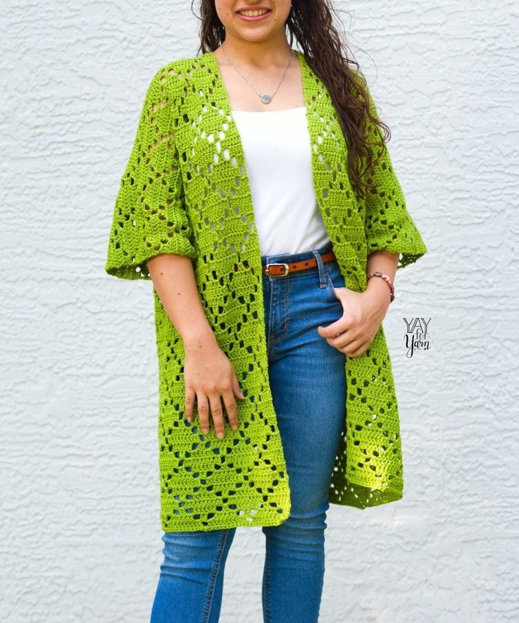 in front of grey / white background, girl stands wearing green crocheted cardigan with white tank and jeans