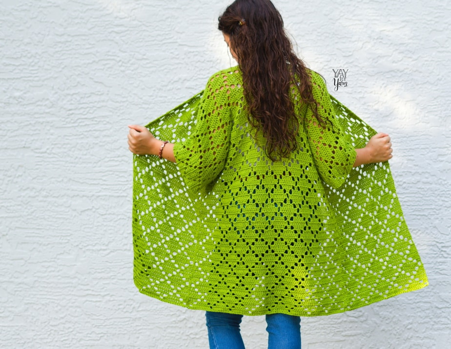 girl opening green crocheted cardigan to show the back