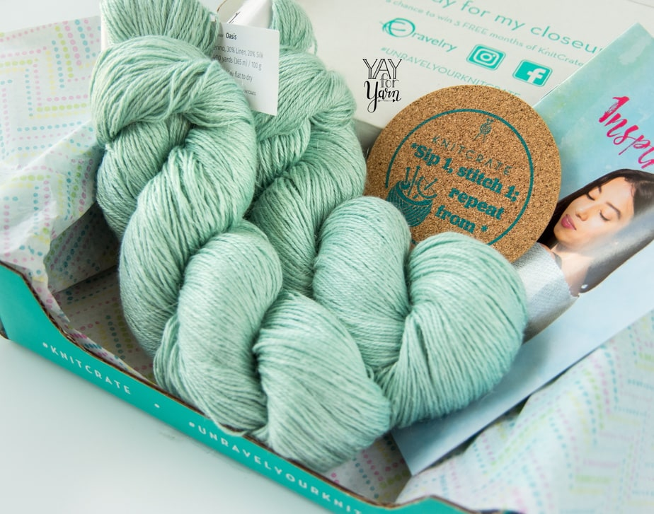 two hanks of blue-green yarn, coaster, and pattern booklet in green knitcrate box