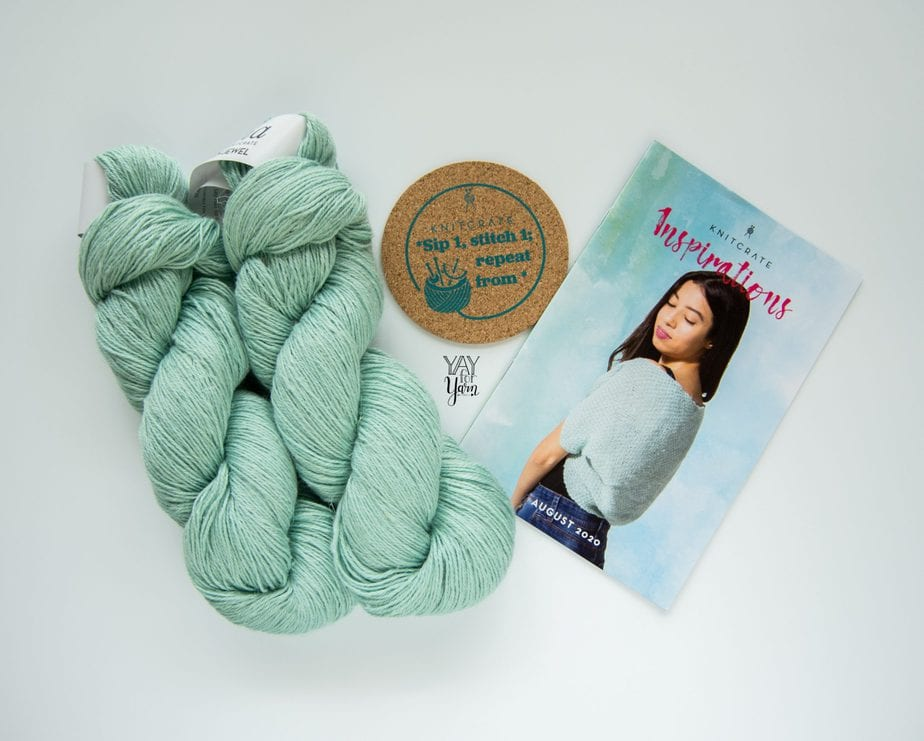 two hanks of pale blue-green yarn with coaster and pattern booklet on white background