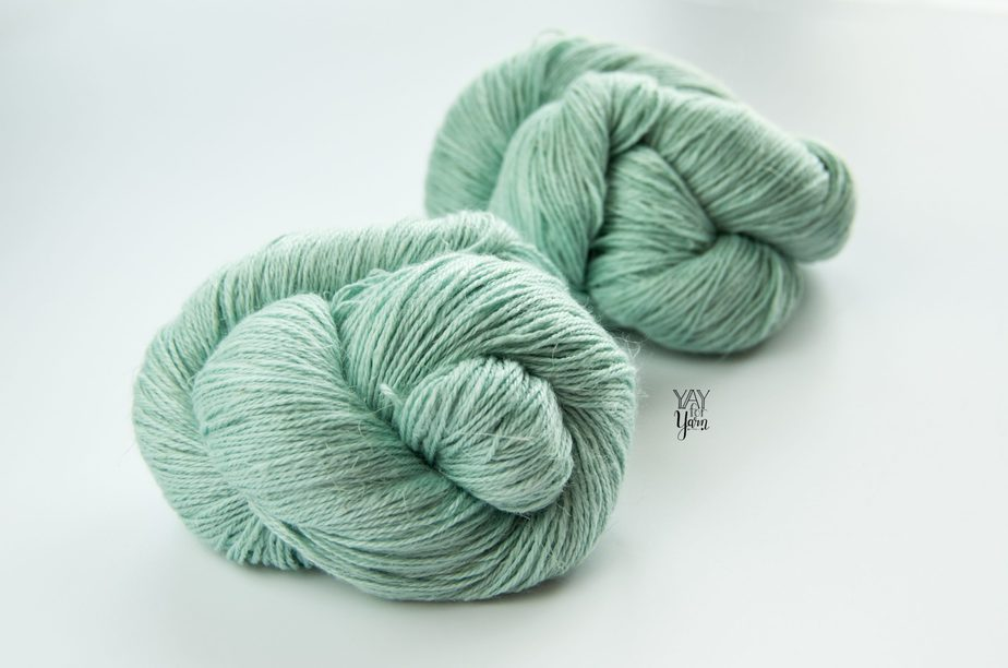 two twisted skeins of pale blue-green silk linen wool yarn on white background