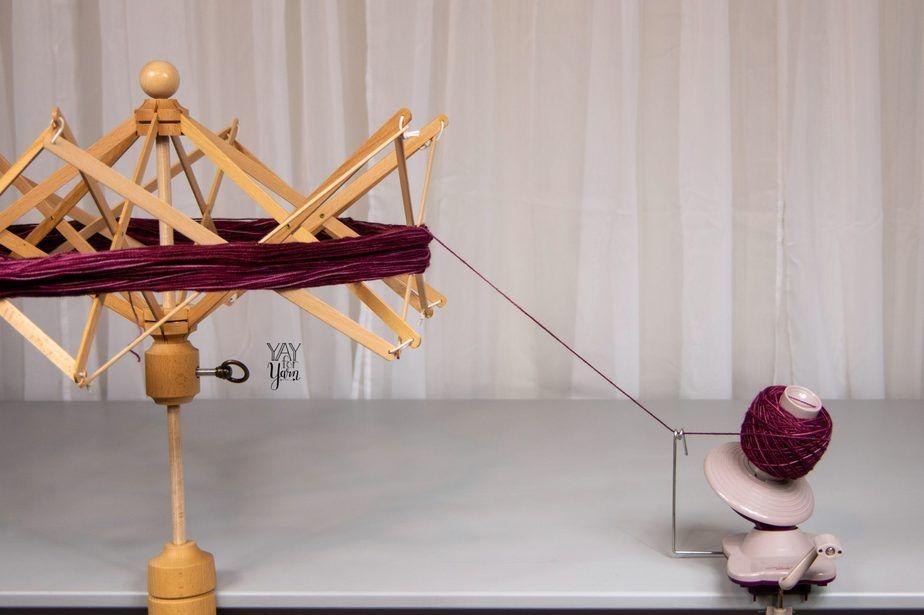 knitpicks birch yarn swift and ball winder on grey table, winding a deep purplish red yarn