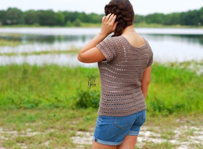 girl standing in front of lake, wearing brown crochet tee with jean shorts, touching braided hair