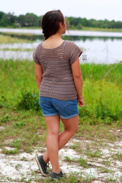girl wearing crochet tee in front of lake