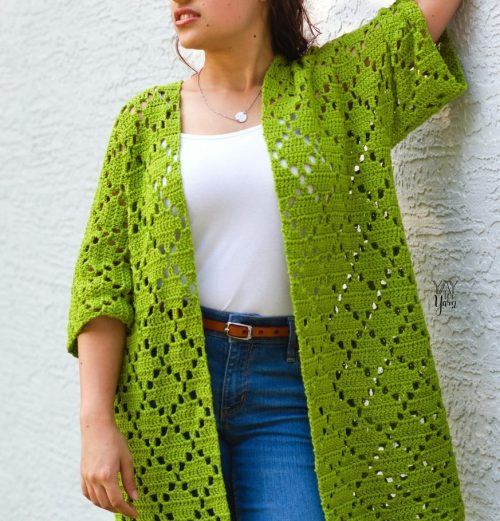 girl leaning against grey wall wearing green crocheted kimono cardigan with white tank and jeans