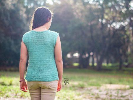 girl wearing light blue-green knitted summer top, walking away