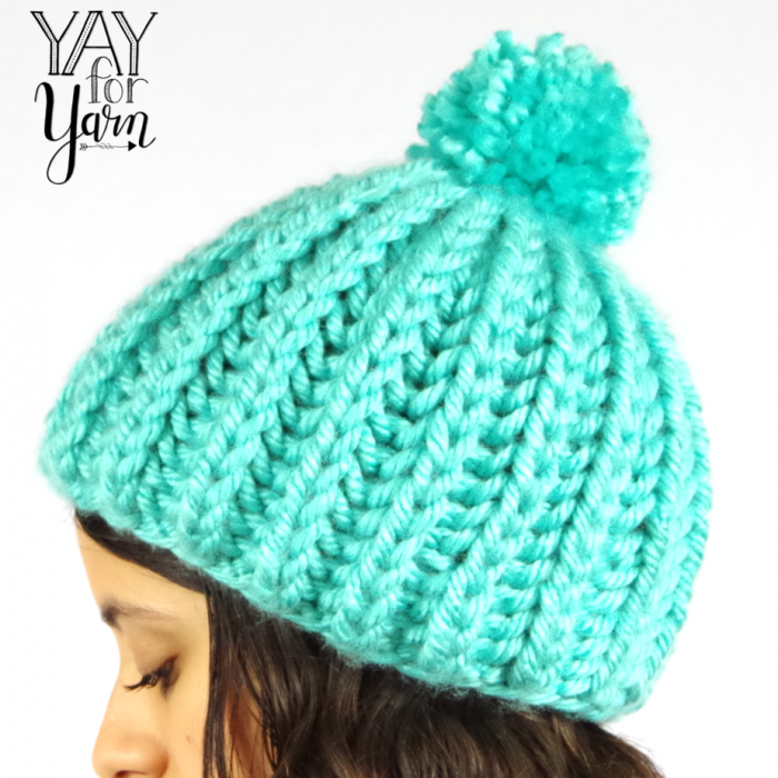 This Super Chunky Pom Pom Hat is a quick and easy project, knit in SHORTCUT Brioche Stitch.