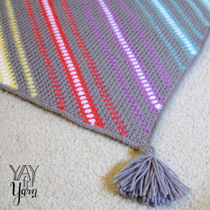 I love putting tassels on the corners of crocheted blankets!  This one is called Watercolor Skies, a C2C Moss Stitch pattern.